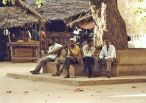 Men sit in the shade of a tree on Lamu island, Kenya