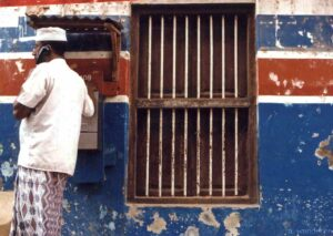 Man in traditional Swahili dress talks on the phone in Mombasa