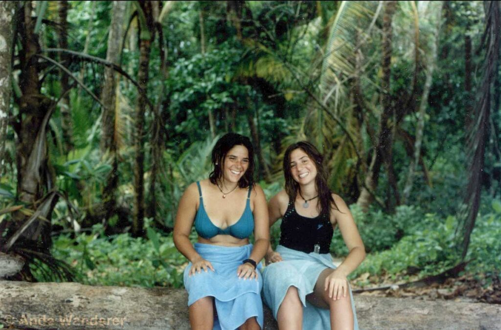 Smiling girls on a beach in front of the rainforest in Costa Rica