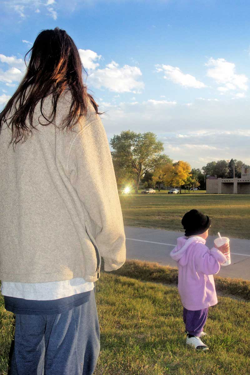 A homeless mother and her toddler look onto the horizon