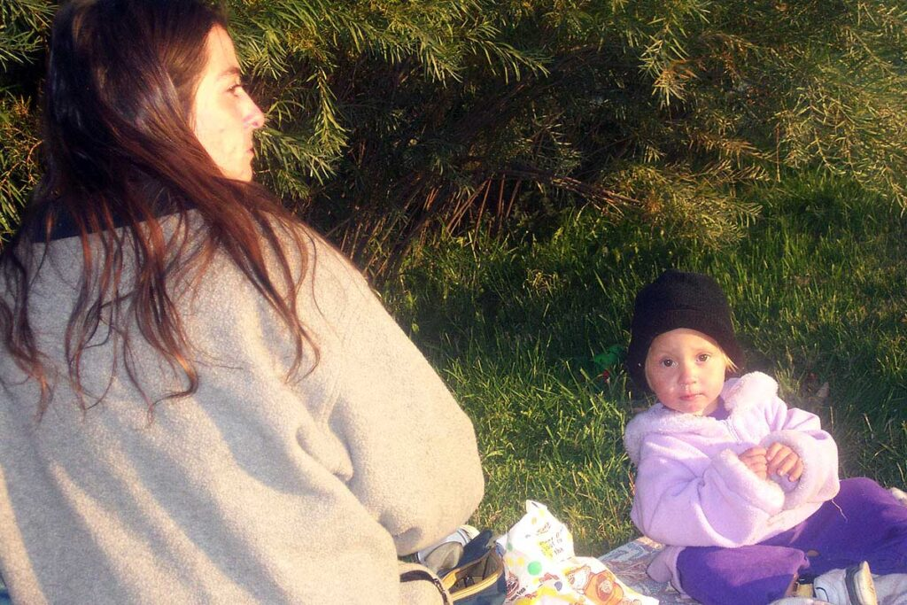A homeless woman and baby sitting outside in a park