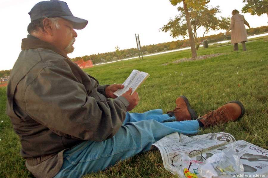 A homeless vet reads a book in Sloan's Lake park in Denver