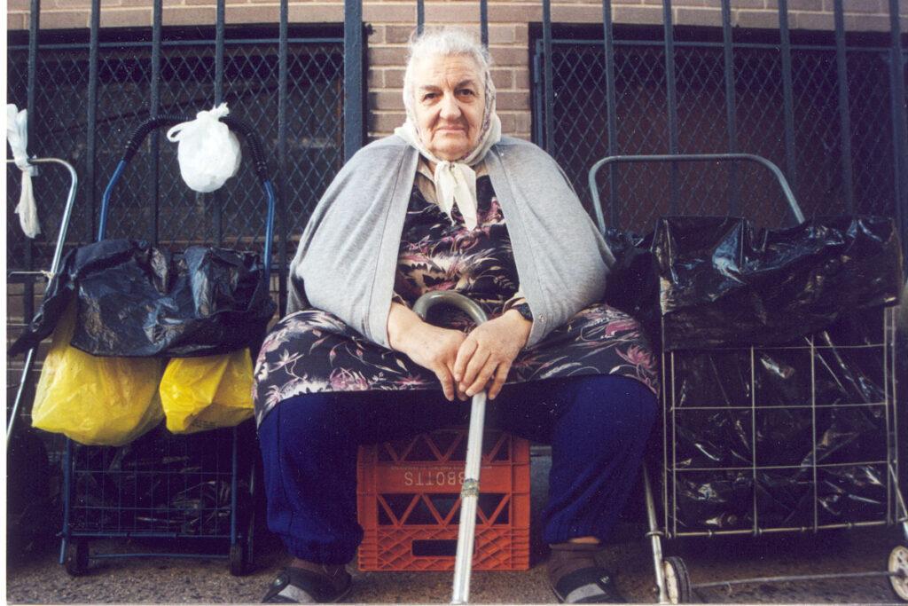 A babushka with her belonging on the sidewalk in New York City